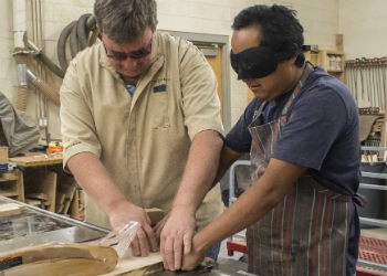 Ray working with student in wood shop